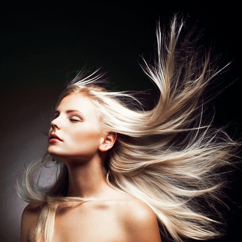 Жена, която си разтваря косата, боядисана с пепелно руса боя